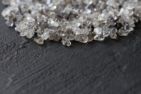 Scattered diamonds on a black background. Raw diamonds and mining, a scattering of natural diamond stones. Graphite quartz. Natural stones and minerals. Copy space for your text. Stock Photo