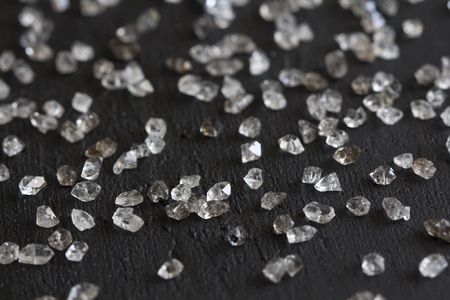 Scattered diamonds on a black background. Raw diamonds and mining, a scattering of natural diamond stones. Graphite quartz. Natural stones and minerals. Фото со стока