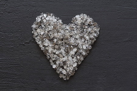 Heart of stones, love. Scattered diamonds on black background. Raw diamonds and mining, a scattering of natural diamond stones. Graphite quartz. Natural stones and minerals. Copy space for your text.