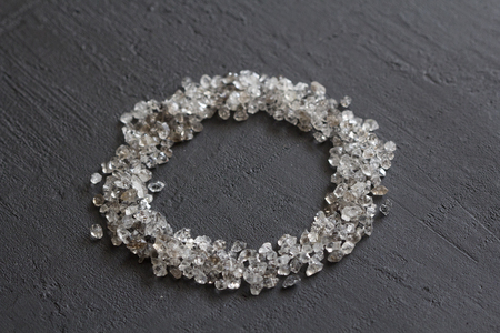 Scattered diamonds on a black background. Raw diamonds and mining, a scattering of natural diamond stones. Graphite quartz. Natural stones and minerals. Frame, cover, circle or oval of stones.