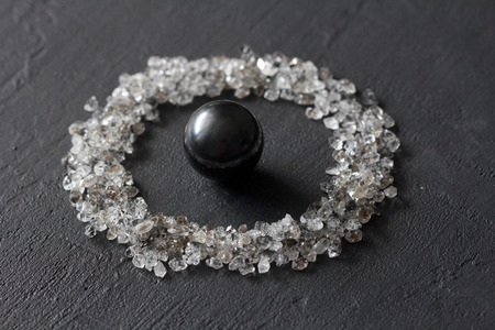 Scattered diamonds on a black background. Raw diamonds and mining, a scattering of natural diamond stones. Graphite quartz. Natural stones and minerals. Stone magnetite, attraction, black hole.