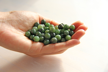 Natural green jade nephrite mineral stones beads. The green jade stone lies in the hands. Hands holding stone on white background. Green and grassy natural background made of round stone beads.