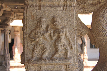 Stone bas-reliefs on the column in Shiva Virupaksha Temple, Hampi. Carving stone ancient background. Carved figures made of stone.   Karnataka, India. Stock Photo - 124444391