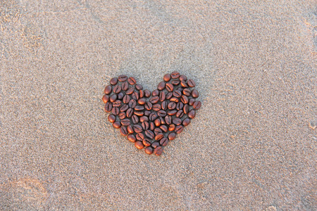 Heart of coffee. Grains of coffee are laid out on sand in the form of heart. Love of coffee. Design with copy space. Top view.