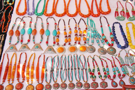 Bright orange and blue turquoise beads are sold on the market in India. Gift souvenir India Tibet Bazaar. Stock Photo
