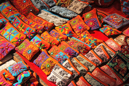 Bright national colored handbags are handmade embroidery cosmetic products sold on the market in India. Gift souvenir India Tibet Bazaar.