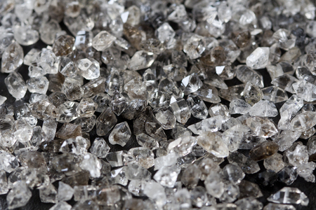 Scattered diamonds on a black background. Raw diamonds and mining, a scattering of natural diamond stones. Graphite quartz. Natural stones and minerals. Stock Photo
