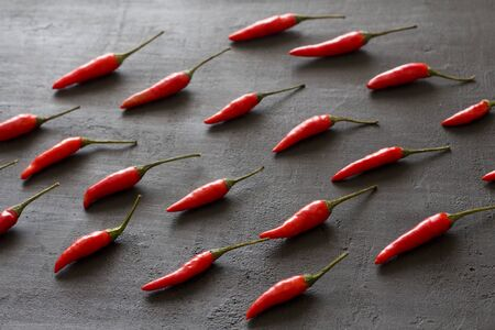 Red Hot Chili Peppers On Black Dark Background on Black Table. A Lot of Red Chilli Peppers. Copy space for your text. Flat lay, top view. Rhythmic image, repetition of a picture or objects in a photo. Standard-Bild