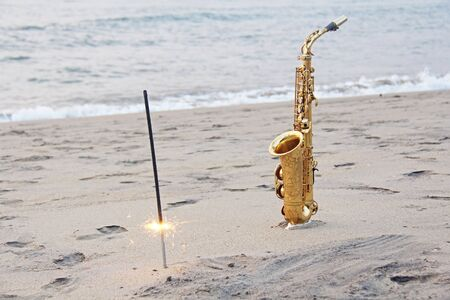 The golden saxophone alto stands on the sand and on the shore, against the background of the sea and Bengal lights. Romantic musical background. Musical cover and holiday. Design with copy space.