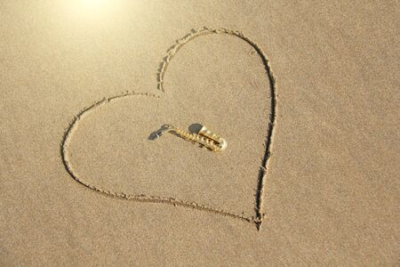 The golden alto saxophone lies inside the heart of the sand, on the beach. Romantic musical background. Musical cover and creative. Design with copy space.