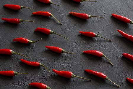 Red Hot Chili Peppers On Black Dark Background on Black Table. A Lot of Red Chilli Peppers. Copy space for your text. Flat lay, top view. Rhythmic image, repetition of a picture or objects in a photo.