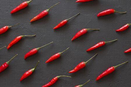 Red Hot Chili Peppers On Black Dark Background on Black Table. A Lot of Red Chilli Peppers. Copy space for your text. Flat lay, top view. Rhythmic image, repetition of a picture or objects in a photo. Фото со стока