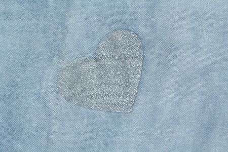 Silver heart on a blue background of cotton fabric. Romantic pastel background. Design with copy space. Denim color. Pastel background. Imagens