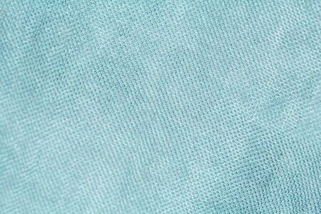 Pastel background. Background made of natural fabric. Texture of natural linen or cotton fabric. The color is turquoise .