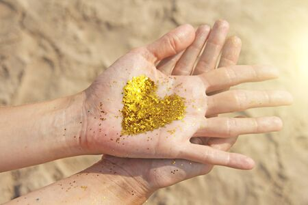 A golden shining heart lies in the hands of the girl. Heart in the palms. Golden heart. Stock Photo