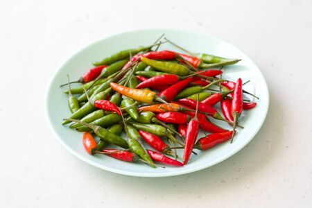 Red Hot Chili Peppers On Modern Background or White Table, on a Round Plate. A Lot of Red Chilli Peppers. Green Hot Chili Peppers. Copy space for your text. Flat lay, top view. Colorful chili pepper. Banque d'images