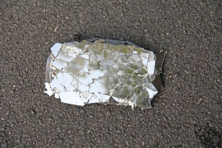 Broken and Cracked Car or Motorcycle Mirror Lies on the Road. Accident on the road. Safe Driving of Transport, Rules of Road Traffic. Stock Photo