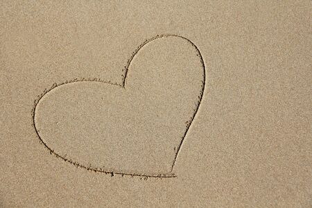 The heart is painted on the sand. Design with copy space. Top view.