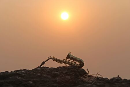The golden alto saxophone lies on a black stone, against a background of sunset. Romantic musical background. Musical cover and creative. Design with copy space.