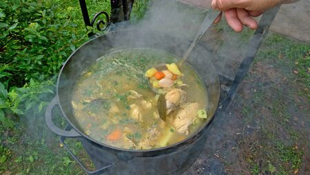 Delicious chicken soup is cooked on an open fire in a black cast-iron pot. A man's hand tries a soup with a ladle. Street food.