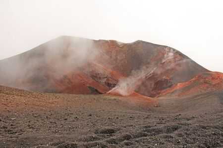 The Etna volcano. The Etna volcano crater. Black Volcanic Earth, Volcanic Lava and Stones.  Dense Fog on Mount Etna. Place for Text. The island of Sicily, Italy.