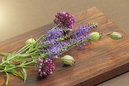 A beautiful summer bouquet, wildflowers, wild onions, Veronica long-leaved violet on a wooden background of black walnut. Minimalism. Beautiful summer wildflowers.