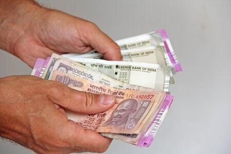 A man's hand holds Indian money and counts them. Paper Indian banknotes in the hands.