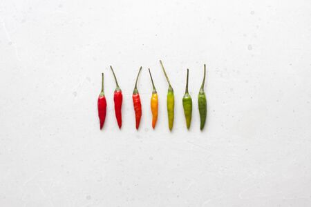 Red Hot Chili Peppers On Background or White Table. A Lot of Red Chilli Peppers. Green, Yellow Hot Chili Peppers. Copy space for your text. Flat lay, top view. Colorful chili pepper rainbow. Gradient. Foto de archivo