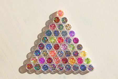 Multi colored Sequins for the design of nails in a Jar. Glitter in jars. Foil for nail service. Photo set. Sparkling beauty shimmer, glitter. Bright background of glitter a triangle. Top view Zdjęcie Seryjne - 129251864