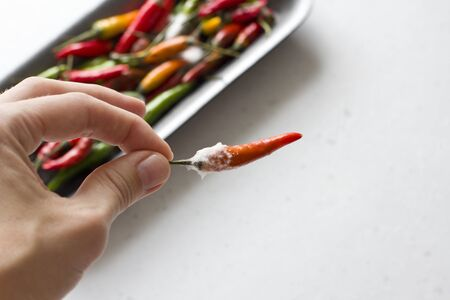 White mold on orange chili peppers, on a modern light gray background. Spoiled food, vegetables. Hand holds chili pepper.