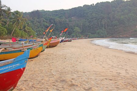 Bright colorful boats with flags for catching fish stood on the shore of the Indian Ocean. India, Goa.