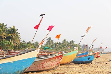 Bright fishing boats stand on the sand in India, GOA. Multicolored Indian boat on the background of the sea. A crow or a bird sits on top of the boat.