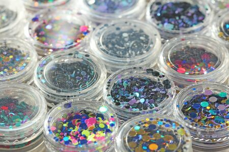 Multi colored Sequins for the design of nails in a Jar. Glitter in jars. Foil for nail service. Photo set. Sparkling beauty shimmer, glitter. Bright background of glitter. Top view. Zdjęcie Seryjne - 129251705