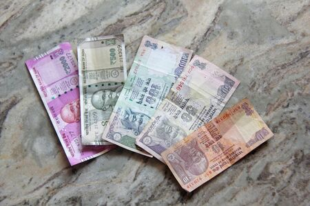 Indian money and banknotes, 2000, 500, 100, 50 and 10 rupees, lie on a marble background.