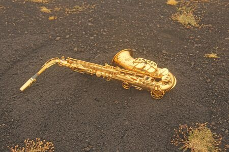 Golden Alto Saxophone Lies on the Black Background. Romantic and Beautiful Saxophone. Place for Text. The Etna volcano. The island of Sicily, Italy. Zdjęcie Seryjne