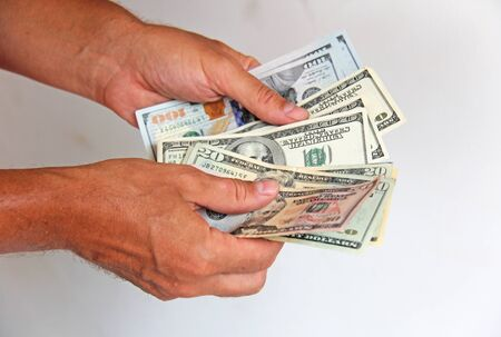 A mans hand holds US dollars and counts them. Paper money dollars in hand.