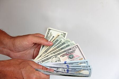 The mans hand holds US dollars, counts them and pays. Paper money dollars in hand.