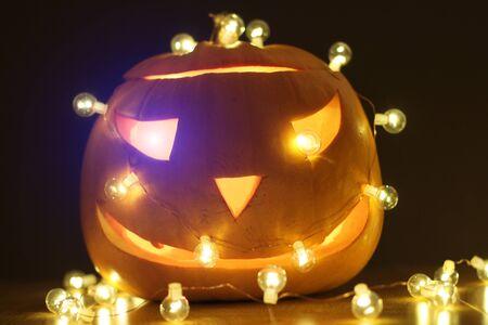 Halloween Pumpkins head. Orange pumpkin with a smile and glowing eyes. Neon.