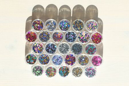 Multi colored Sequins for the design of nails in a Jar. Glitter in jars. Foil for nail service. Photo set. Sparkling beauty shimmer, glitter. Bright background of glitter. Top view. Zdjęcie Seryjne - 129251510