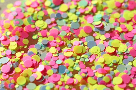 Multi colored Sequins for the design of nails. Glitter. Foil for nail service. Sparkling beauty shimmer, glitter. Bright background of glitter confetti neon. Top view. Zdjęcie Seryjne - 129251365