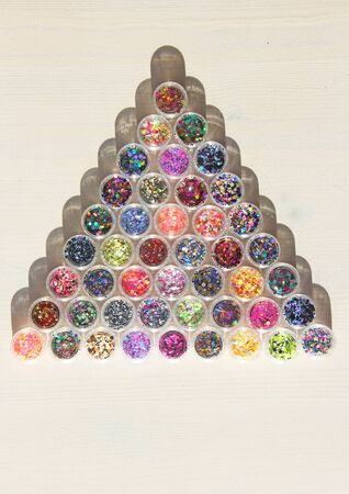 Multi colored Sequins for the design of nails in a Jar. Glitter in jars. Foil for nail service. Photo set. Sparkling beauty shimmer, glitter. Bright background of glitter a triangle. Top view Zdjęcie Seryjne - 129251368