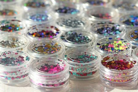 Multi colored Sequins for the design of nails in a Jar. Glitter in jars. Foil for nail service. Photo set. Sparkling beauty shimmer, glitter. Bright background of glitter. Top view. Stock fotó
