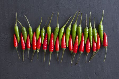 Red Hot Chili Peppers On Black Dark Background on Black Table. A Lot of Red Chilli Peppers. Copy space for your text. Flat lay, top view. Red and Green Chili Peppers. Penetration, erotica.