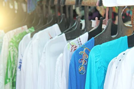 Clothes India hangs on hangers and is sold. White and blue cotton womens shirts are sold in the market of the bazaar in India.