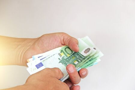 The mans hand holds the euro, considers them and pays. Paper money euros in the hands.