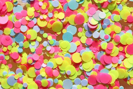 Multi colored Sequins for the design of nails. Glitter. Foil for nail service. Sparkling beauty shimmer, glitter. Bright background of glitter confetti neon. Top view.