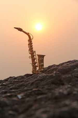 The golden saxophone alto stands on a black stone, against a background of sunset. Silhouette of saxophone against the sky. Romantic musical. Musical cover and creative. Design with copy space.