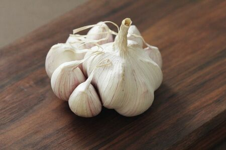 Garlic. The whole lies on the wooden background. Rustic style. Minimalism.