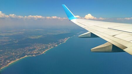 Airplane wing view out of the window on the cloudy sky The Earth and the blue sea background. Holiday vacation background. Wing of airplane flying above the clouds in the sky. Black Sea, Bulgaria.