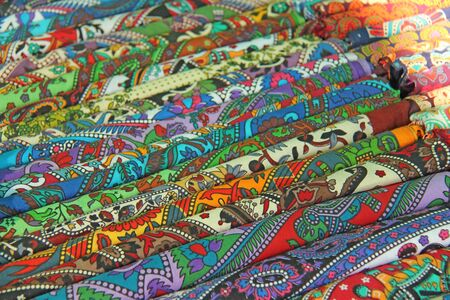 Bright colored fabrics India ornaments and oriental drawings. It is built on the market. Hand Embroidery India. Tablecloths of different colors are sold at the bazaar in India, Goa.